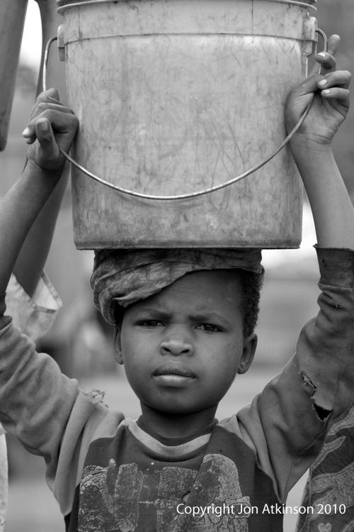 Black white 7 girl with bucket uganda