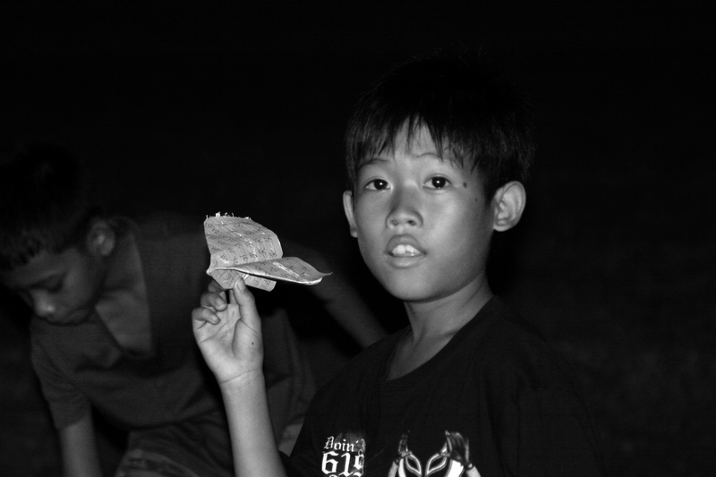 Boy with paper plane at a night market