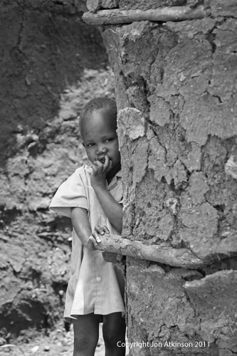 Child outside of dung covered hut, Kenya.